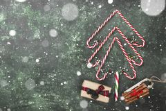 Christmas tree from candy canes and box with gift on a green bac. Kground. Top view, copy space. Snow Stock Photography