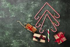 Christmas tree from candy canes and boxes with gifts on a green Stock Image