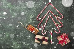 Christmas tree from candy canes and boxes with gifts on a green. Background. Top view, copy space. Snow Stock Photography