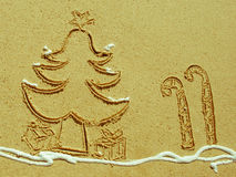 Christmas Tree and Candy Stick drawing in sand. A Christmas tree and candy sticks drawing in the sand, with shaving cream acting as snow Stock Photos
