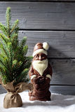 Christmas tree and chocolate santa clause on heap of snow against wooden background Royalty Free Stock Image