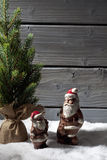 Christmas tree and chocolate santa clauses on heap of snow against wooden background Royalty Free Stock Image