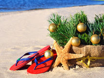 Christmas tree with christmas balls, slippers and starfish on th Stock Image