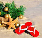 Christmas tree with christmas balls, slippers and starfish on th Stock Photography