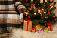 Christmas Tree and christmas gift boxes in the interior, close up Stock Photos