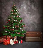 Christmas tree with Christmas gifts. Many gifts are under the Christmas tree next to the suitcases stock photography