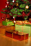 Christmas tree with christmas gifts in red room Stock Photography