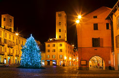 Christmas tree on city square in Alba, Italy. Illuminated and decorated Christmas Tree on city central square surrounded by old houses and medieval towers at Royalty Free Stock Image
