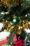 Christmas tree closeup. Christmas decorations on a tree including tinsel and ball with crackers Royalty Free Stock Image