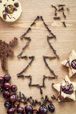 Christmas tree of cloves with rose hips and linzer cookies Stock Photo