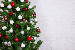 Christmas tree with colorful balls over white brick wall Stock Images