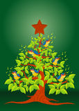 Christmas tree with colorful birds singing and wooden star on green background Stock Photo