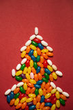 Christmas tree from colorful candies on red paper background. Stock Image