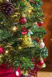 Christmas tree with colorful ornaments. Green christmas tree decorated with lights, bells, colored balls, stars and pine cones royalty free stock photography