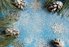 Christmas tree and cones in the snow on a blue background and snow for the New Year`s greeting card with snowflake stock photos