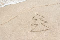 Christmas tree contour with star and wave on the beach Stock Image