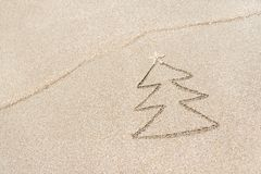Christmas tree contour with star and wave on the beach Royalty Free Stock Photography