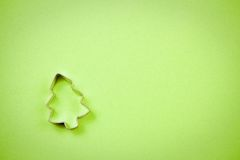 Christmas tree cookie cutter. On a sheet of textured green paper, room for copy. Focus is on the upper brim of cutter Royalty Free Stock Photography