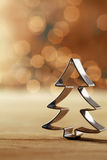 Christmas tree cookie cutter decoration. Shiny silver metallic Christmas tree cookie cutter decoration standing upright aginst a sepia background with a bokeh of Royalty Free Stock Photo