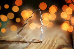 Christmas tree cookie cutter on wooden background with a bokeh. Royalty Free Stock Photos