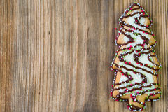 Christmas tree cookie on a natural wooden background. Single cookie in a shape of christmas tree on a natural wooden background Royalty Free Stock Photography