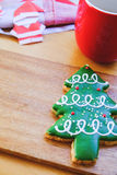 Christmas tree cookie on wood plate. With background of paper Santa and coffee mug Stock Photos