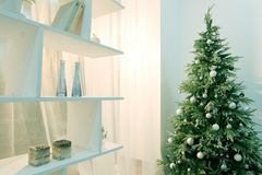 Christmas tree in the corner of the room next to a white rack with shelves. Modern decor in the house for the holiday. Abstract ba stock photo