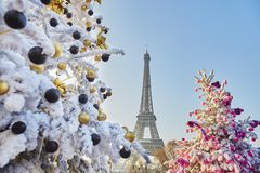 Christmas tree covered with snow near the Eiffel tower in Paris. Decorated Christmas trees covered with snow near the Eiffel tower in Paris, France royalty free stock photo