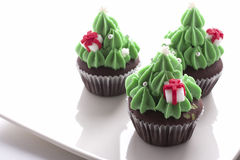 Christmas tree cupcake. Decorating with gift box on white dish royalty free stock photos