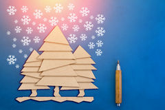 Christmas tree cut out from paper and doodle snow flake on blue. Paper background Stock Photo