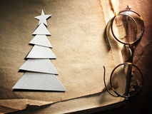Christmas tree cut out from paper and glasses. On old paper background Royalty Free Stock Image
