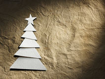 Christmas tree cut out from paper. On old paper background Stock Image