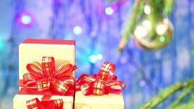 The Christmas tree decorated with balls is blurred and the focus turns to gifts with red bows. stock footage