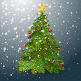 The Christmas tree is decorated with balls, a garland, snowfall and a golden star. Fir tree on gblue winter background. Stock Image