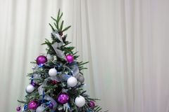 Christmas tree decorated with balls and garlands on a background of white curtains. Copy space. Traditional decor for celebrating royalty free stock images