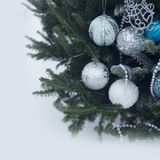 White, silver and blue baubles on a Christmas tree. A Christmas tree decorated with balls made of glass in white, silver and blue colors against white backgroun Royalty Free Stock Photo