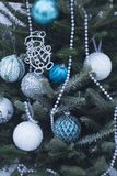 White ansd blue aubles and beads on a Christmas tree. A Christmas tree decorated with balls made of glass in white, silver and blue colors. White pearl beads on Stock Photography