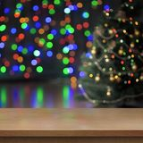 Christmas tree decorated behind empty wood table or shelf. Decorated Christmas tree lights behind empty wood table or shelf royalty free stock photography