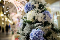 Christmas tree decorated with flowers. Christmas tree decorated with purple and white flowers Royalty Free Stock Photo