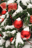 Christmas tree decorated in front of the house. Fluffy snow flakes fall around an outdoor christmas tree with ornaments and  Christmas-tree decorations Stock Photos