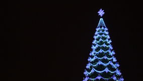 Christmas tree decorated with garlands and lanterns. With a place for text on a background. At night stock footage