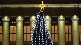 Christmas tree decorated with garlands and lanterns. Theater on a background. At night stock video