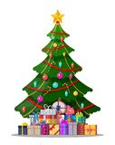 Christmas tree decorated and gift boxes. Christmas tree decorated with colorful balls, garland lights, golden star. Lots of gift boxes. Spruce, evergreen tree Royalty Free Stock Image