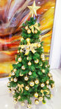 Christmas tree decorated in gold and Christmas ornaments and gold star on top Royalty Free Stock Image