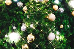 Christmas tree decorated with Christmas gold and silver ball han. Ging on tree with sparkling and twinkling lights in holiday and festive background Royalty Free Stock Image