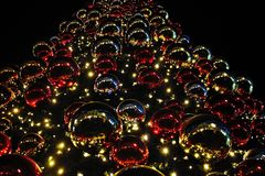 Christmas tree decorated with lights and colored spheres stock image