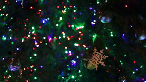 Christmas tree decorated with lights, toys at. Decorated in different lights, toys, snowflakes Christmas tree standing in the street and sways in the wind stock video
