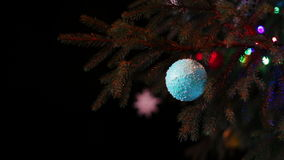 Christmas tree decorated with lights, toys at. Decorated in different lights, toys, snowflakes Christmas tree standing in the street and sways in the wind stock video footage