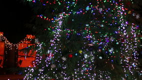 Christmas tree decorated with lights, toys at. Decorated in different lights, toys, snowflakes Christmas tree standing in the street and sways in the wind stock footage