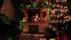 Christmas tree decorated in living room interior with fireplace, armchair, window